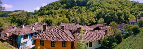 Traditional authentic houses with stone roofs in the Etar Architectural-Ethnographic Complex. Panorama of traditional authentic houses with stone roofs in the Royalty Free Stock Images