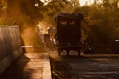 Traditional auto three wheeler is running on a road in the afternoon. A traditional auto three-wheeler vehicle is running on a busy road in the afternoon Stock Photo