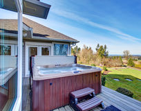Traditional back deck with tall windows, and jacuzzi tub. Royalty Free Stock Images
