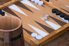 Traditional backgammon game. Being played in tavern handmade dice, wooden table, ale mug stock photography