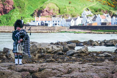 Traditional bagpiper in full dress code near Pennan. Traditional bagpiper in the scottish highlands near Pennan Stock Photos