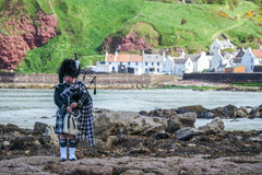 Traditional bagpiper in full dress code near Pennan Royalty Free Stock Photos