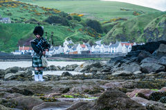 Traditional bagpiper in full dress code near Pennan. Traditional bagpiper in the scottish highlands near Pennan Royalty Free Stock Photo