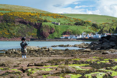 Traditional bagpiper in full dress code near Pennan. Traditional bagpiper in the scottish highlands near Pennan Stock Photo