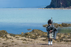 Traditional bagpiper in full dress code near Pennan. Traditional bagpiper in the scottish highlands near Pennan Royalty Free Stock Image