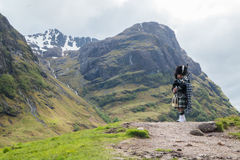 Traditional bagpiper in the scottish highlands. Near Glencoe royalty free stock photography