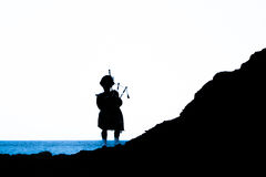 Traditional bagpiper in the scottish highlands. Near Pennan Stock Photo