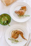Traditional baked rabbit with herbs. Traditional Spanish recipe of rabbit baked with herbs, olive oil and white wine. Two plates with meat and bowl with fresh Stock Photography