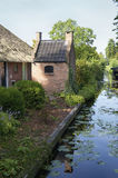Traditional bakehouse in Giethoorn. A traditional bakehouse in the idyllic village Giethoorn. A small canal with plants and a boat Stock Photo