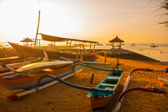 Traditional Balinese boats and pavilion in Sanur beach in the morning at dawn, Bali, Indonesia. Royalty Free Stock Photo