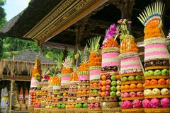 Traditional Balinese ceremonial temple offerings: big fruits and rice pyramids on golden plates decorated with flowers Stock Images