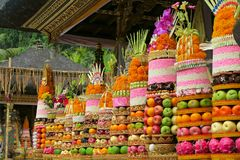 Traditional Balinese ceremonial temple offerings: big fruits and rice pyramids on golden plates decorated with flowers Royalty Free Stock Images