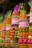 Traditional Balinese ceremonial temple offerings: big fruits and rice pyramids on golden plates decorated with flowers Stock Photos