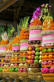 Traditional Balinese ceremonial temple offerings: big fruits and rice pyramids on golden plates decorated with flowers Stock Photography