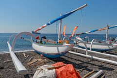 Traditional Balinese fisherman fishing boat on the beach with black volcanic sand. Sunny day with blue sky in tropical paradise. F. Ishing nets stored under the royalty free stock image