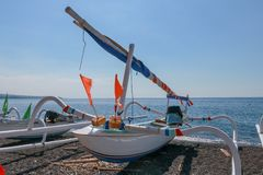 Traditional Balinese fisherman fishing boats on a beach with black volcanic sand. Sunny day with blue sky in tropical paradise. Fi. Shing nets stored under the royalty free stock images