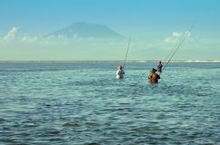 Traditional Balinese fishermen standing in shallow water at low tide on the beach at Nusa Dua Royalty Free Stock Photo