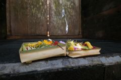 Traditional Balinese flower offerings to God with incense. Royalty Free Stock Image
