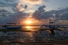 Traditional balinese jukung at sunrise on Sanur Beach. Sanur is Bali`s oldest upscale resort area and is a mature beach-side town Royalty Free Stock Photography