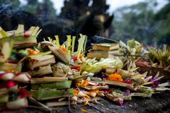 Traditional balinese offerings to gods in Bali with flowers and aromatic sticks.Bali, Indonesia, Tirta Empul temple. Culture. close up royalty free stock photo