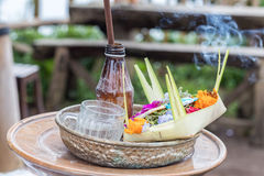 Traditional balinese offerings to gods in Bali with flowers and aromatic sticks. Tropical island Bali, Indonesia. Royalty Free Stock Images