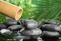 Traditional bamboo fountain with zen stones. Space for text royalty free stock image