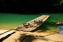 Traditional bamboo raft floats over the clear river in the morning. With reflection of the forest and mountains Royalty Free Stock Images