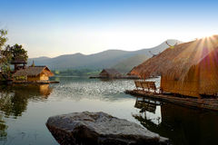 Traditional bamboo raft houses on the lagoon  with mountain background at khao wong reservoir Suphanburi province Thailand. Traditional bamboo raft houses on the Stock Image