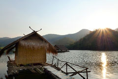Traditional bamboo raft houses on the lagoon  with mountain background at khao wong reservoir Suphanburi province Thailand. Traditional bamboo raft houses on the Stock Photo