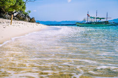 Traditional banca boat in clear water at sandy Beach near El Nido, Philippines Royalty Free Stock Photo