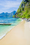 Traditional banca boat in clear water at sandy beach near El Nido, Philippines Stock Photography
