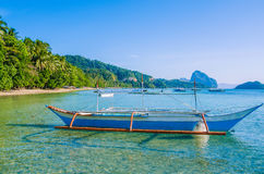 Traditional banca boat in clear water at sandy Corong Beach in El Nido, Philippines Royalty Free Stock Image
