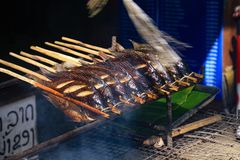 Traditional barbecue street food with fish in a row on wooden skewers on charcoal grill - Vang Vieng, Laos stock image