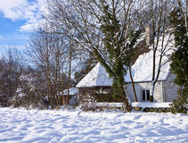 Traditional Bavarian house with imposing slanted roof covered by snow in Stock Photography