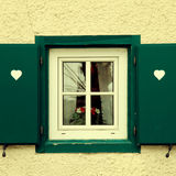 Traditional bavarian small window with green shutters royalty free stock images