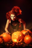Traditional. Beautiful red-haired witch casts a spell over pumpkins. Halloween royalty free stock photos