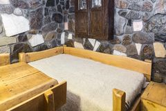 Traditional Bed. Traditional Romanian wooden bed covered by a whool blanket cerga in a hostel chalet in Transylvania Royalty Free Stock Photo