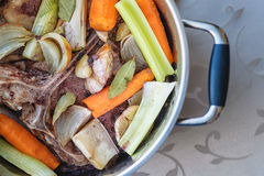 Traditional beef broth with vegetable, bones and ingredients in pot, cooking recipe Stock Photography