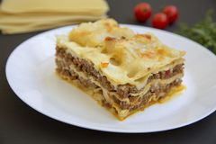 Traditional beef lasagne on a white round plate, black background. Side view royalty free stock images