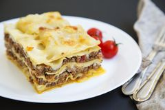 Traditional beef lasagne on a white round plate on black background,. Side view royalty free stock photo