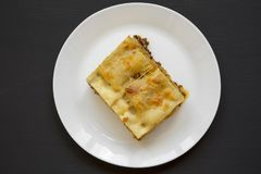 Traditional beef lasagne on a white round plate on black background, top view. Flat lay. From above royalty free stock images