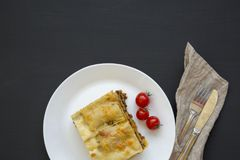 Traditional beef lasagne on a white round plate on black background, top view. Flat lay. Copy space royalty free stock photos