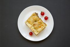 Traditional beef lasagne on a white round plate on black background, top view. Flat lay. From above stock photos