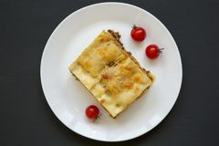 Traditional beef lasagne on a white round plate on black background, top view. Flat lay. From above stock photography
