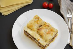 Traditional beef lasagne on a white round plate, black background,. Top view royalty free stock photos