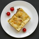 Traditional beef lasagne on a white round plate on black surface, overhead surface, overhead view. Flat lay. From above, top view. Traditional beef lasagne on a royalty free stock images