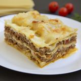 Traditional beef lasagne on a white round plate on black surface, side view. Close-up. Traditional beef lasagne on a white round plate on black surface, side royalty free stock image