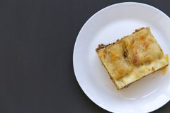 Traditional beef lasagne on a white round plate, dark background, top view. Flat lay, from above. Copy space stock photo