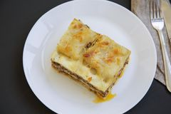 Traditional beef lasagne on a white round plate, dark background,. Top view royalty free stock photo