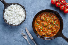 Traditional Beef Madras Indian spicy lamb food with rice and tomatoes in cast iron pan. On blue table background. Delicious India culture restaurant dish royalty free stock images